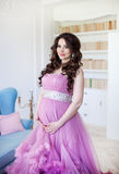 Pregnancy, motherhood and expectation concept - a pregnant woman dressed in pink evening dress smiles Royalty Free Stock Image