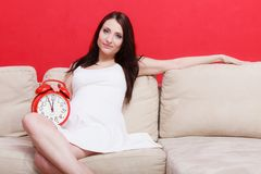 Pregnant woman sitting on sofa holding clock Stock Image