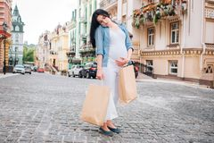 Pregnancy, motherhood, people and expectation concept - close up of pregnant woman with shopping bags at city street stock images