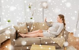 Pregnant woman taking smartphone selfie at home Stock Photo