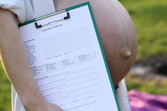 Pregnancy. Naked pregnant woman's belly. A woman holds a medical card Stock Photo