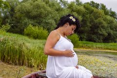 Pregnancy and Nature concept. Pregnant woman resting on the rive stock photography