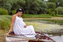 Pregnancy and Nature concept. New life. Pregnant woman resting o. Pregnancy and Nature concept. New life. Beautiful Pregnant woman resting on the river stock photo