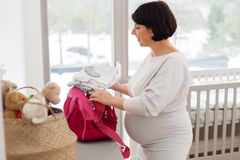Pregnant woman packing bag for maternity hospital. Pregnancy, nursery and people concept - happy pregnant middle-aged woman packing bag for maternity hospital at stock image