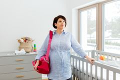 Pregnant woman with bag for maternity hospital. Pregnancy, nursery and people concept - pregnant middle-aged woman with bag for maternity hospital at home royalty free stock photography