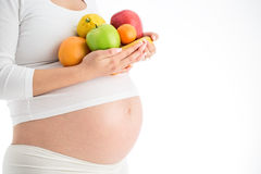 Pregnancy and nutrition diet - pregnant woman with fruits isolated on white background stock image
