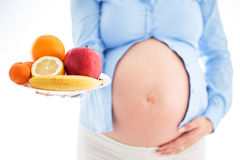 Pregnancy and nutrition diet - pregnant woman with plate of fruits isolated on white background. Pregnancy and nutrition diet - pregnant woman with fruits royalty free stock images