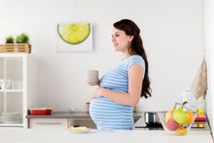Happy pregnant woman with mug and cake at home Royalty Free Stock Image