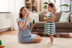 Pregnant mother and daughter blowing soap bubbles royalty free stock photos