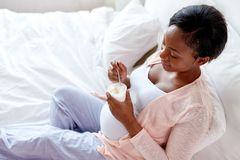 Pregnant woman eating yogurt in bed. Pregnancy, people and food concept - happy pregnant african american woman eating yogurt in bed at home Stock Images