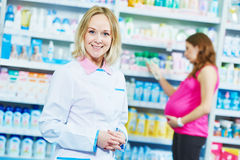 Pregnancy and pharmaceutics. pharmaceutist with pregnant on background at store Royalty Free Stock Photo
