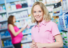 Pregnancy and pharmaceutics. pharmaceutist with pregnant on background at store Royalty Free Stock Images