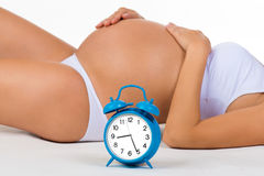 Pregnancy. Pregnant belly with alarm clock. Soon birth. Royalty Free Stock Images