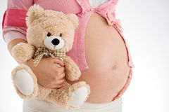 Pregnancy. Pregnant woman holding teddy bear toy in his hand, st Royalty Free Stock Images