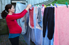 Pregnancy - pregnant woman housework. Pregnant housewife woman doing housework pegging out washing to dry on clothes line during pregnancy.Concept photo of Stock Photo