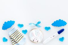 Pregnancy and preparation for childbirth. Babyshower. Pregnancy test near socks and hearts white background top view. Pregnancy and preparation for childbirth royalty free stock images