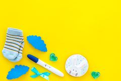 Pregnancy and preparation for childbirth. Babyshower. Pregnancy test near socks and hearts yellow background top view. Pregnancy and preparation for childbirth stock photography