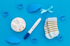 Pregnancy and preparation for childbirth. Babyshower. Pregnancy test near socks and hearts blue background top view. Pregnancy and preparation for childbirth stock images