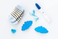 Pregnancy and preparation for childbirth. Babyshower. Pregnancy test near socks and hearts white background top view. Pregnancy and preparation for childbirth stock photos