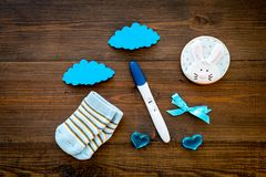 Pregnancy and preparation for childbirth. Babyshower. Pregnancy test near socks and hearts wooden background top view. Pregnancy and preparation for childbirth royalty free stock image