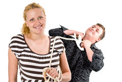 Pregnancy Responsibilities. A conceptual image of a pregnant woman keeping her husband close to her with a rope tied to him, depicting couple's responsibility in Stock Photography