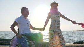 Pregnancy, summer holidays, disabled man, pregnant girl and kid with balloons walk at beach in backlight, daddy. In wheelchair with daughter and wife on stock footage