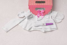 Pregnancy test and baby clothes. Beautiful still life on a plush blanket. Preparing for the meeting with the baby royalty free stock photography