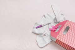 Pregnancy test and baby clothes. Beautiful still life on a plush blanket. Preparing for the meeting with the baby royalty free stock photos