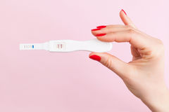 Pregnancy test. Beautiful female hand with red fingernails holding positive pregnancy test isolated on pink background. Motherhood, pregnancy, birth control stock image