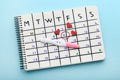 Pregnancy test with calendar and hearts. Pregnancy test with paper calendar and red hearts on blue background royalty free stock photos