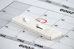 Pregnancy test and a circled date - close up Stock Images