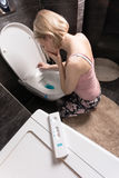 Pregnancy test in the foreground and sad sick woman sitting on her knees over the toilet in the bathroom. royalty free stock photos