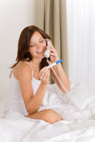 Pregnancy test - happy woman on phone. Positive result stock image