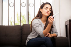 Pregnancy test at home. Beautiful young woman reading a pregnancy test while sitting in a couch at home royalty free stock image