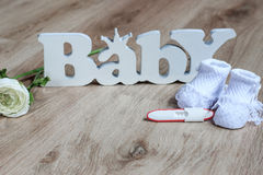 Pregnancy test. Knitted baby socks on a wooden surface stock images