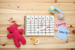 Pregnancy test with calendar and toys. Pregnancy test with paper calendar and toys on wooden table royalty free stock image