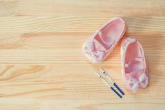 Pregnancy test and pink baby shoes for little girl. Stock Photos