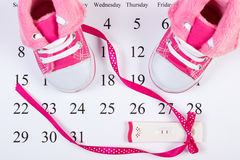 Pregnancy test with positive result and baby shoes on calendar, expecting for baby Stock Photo