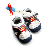 Pregnancy test positive result with baby shoes and present red r Royalty Free Stock Photography