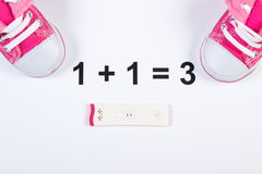 Pregnancy test with positive result and baby shoes on white background, expecting for baby Stock Images