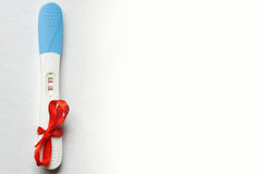 Pregnancy test positive result on clinic table present red ribbo Stock Photography