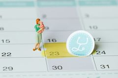 Pregnancy test with positive result. And clothing for newborn on calendar stock images