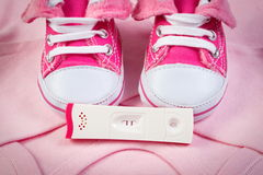 Pregnancy test with positive result and clothing for newborn, expecting for baby Royalty Free Stock Images