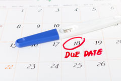 Pregnancy test with positive result lying on calendar background. Circle due date 18th, soft focus Royalty Free Stock Photo