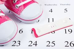 Pregnancy test with positive result and pink baby shoes on calendar, expecting for baby. Pregnancy test with positive result and pink baby shoes lying on royalty free stock images