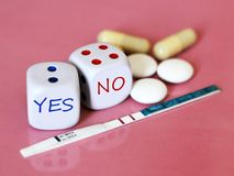 Pregnancy test positive with two stripes and contraceptive pill. The dice on pink background. Health Stock Photo