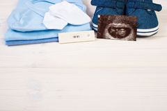 Pregnancy test, ultrasound scan of baby and clothing for newborn, expecting for baby. Pregnancy test with positive result, ultrasound scan of baby and clothing stock image
