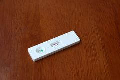 Pregnancy test on wooden background, two red mark the meaning is royalty free stock images