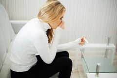 Pregnancy test. Worried sad woman Looking at a Pregnancy Test after result.  royalty free stock photo