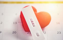 Pregnancy Tests Pregnant woman concept positive result two lines planning a baby motherhood and healthcare and red heart stock images